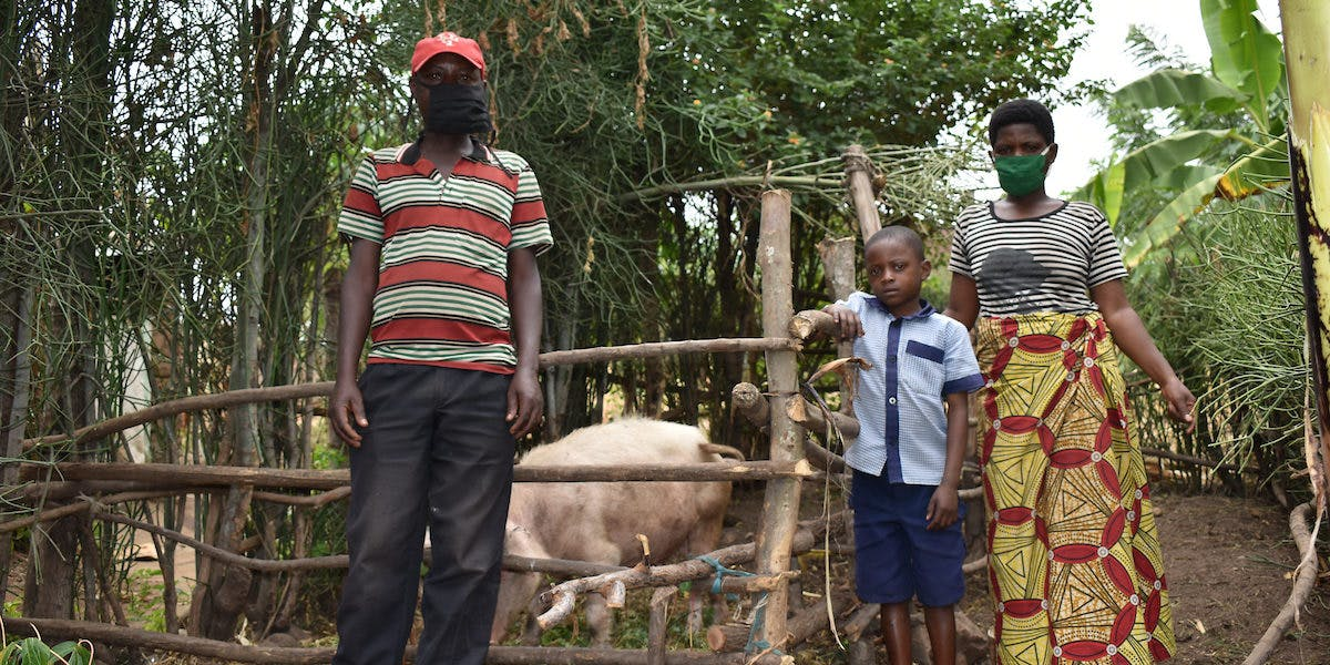 Family from Rwanda standing in front of their pig pen
