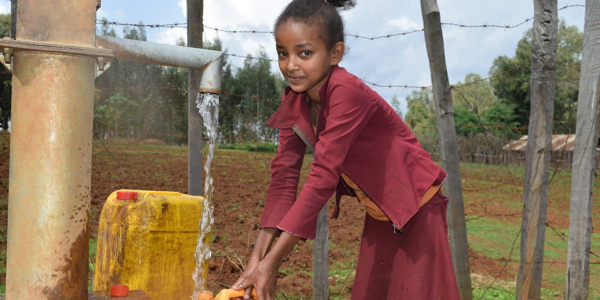 Ethiopian child has access to clean water using a hand dug well.