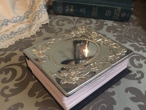 Silver wedding album with Bible in the background