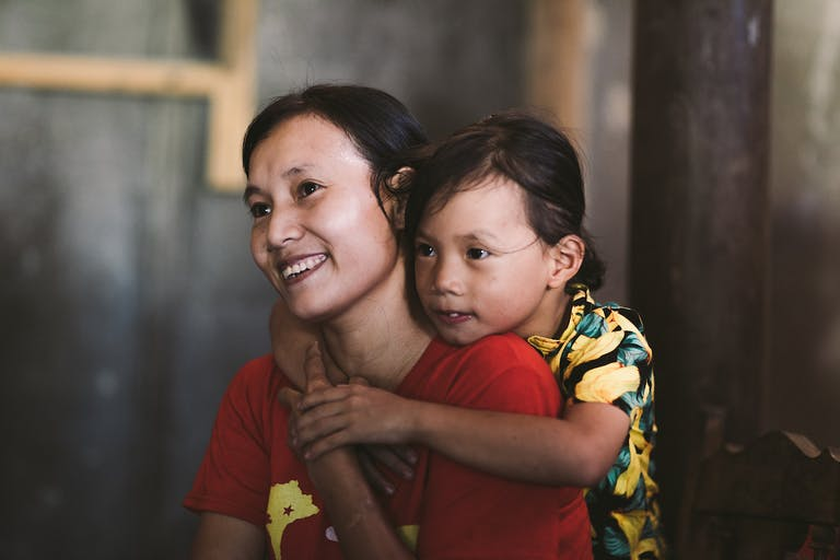 Vietnamese woman smiling with young child hugging her