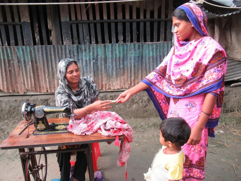 woman at sewing matching outdoors receiving money from another woman with a child