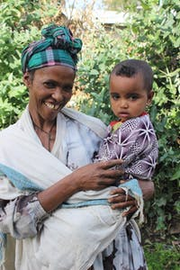 Ethoipian mother smiling and holding 18 month old baby
