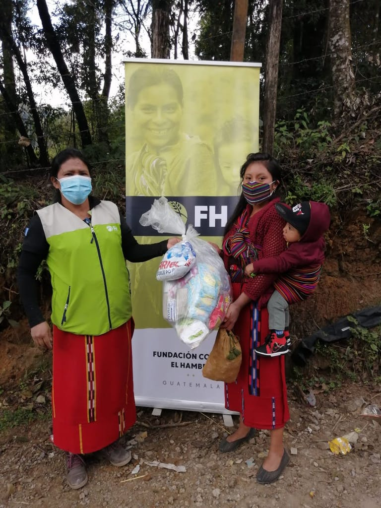two women in front of FH sign with one woman carrying relief supplies