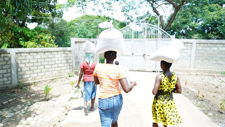 three women walking away from the camera carrying bags of relief food