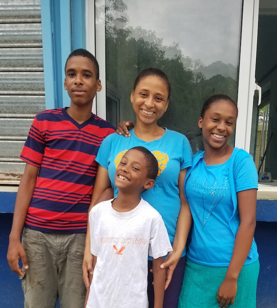 Esther and her three children standing in front of their community clean water system.