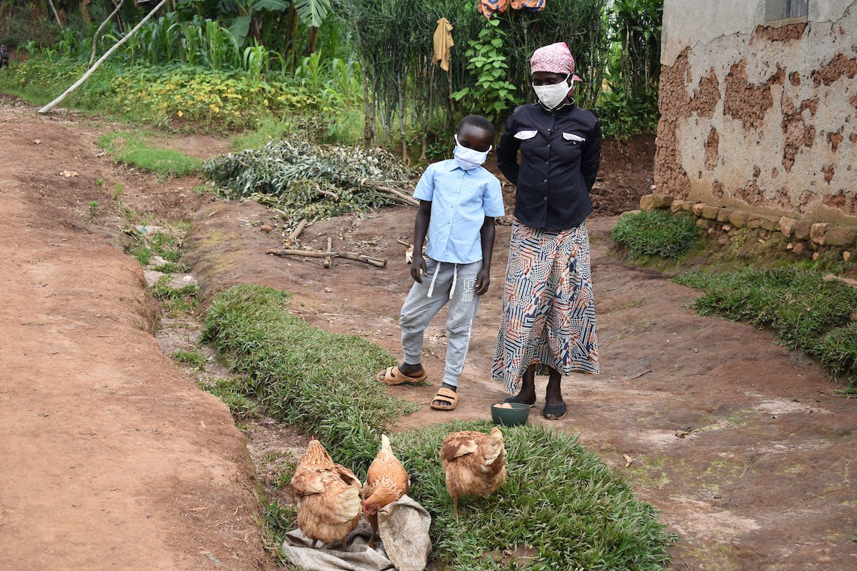 Mother and child standing together next to their chickens.