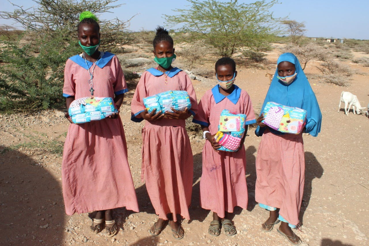 Young school girls holding their Dignity kits.