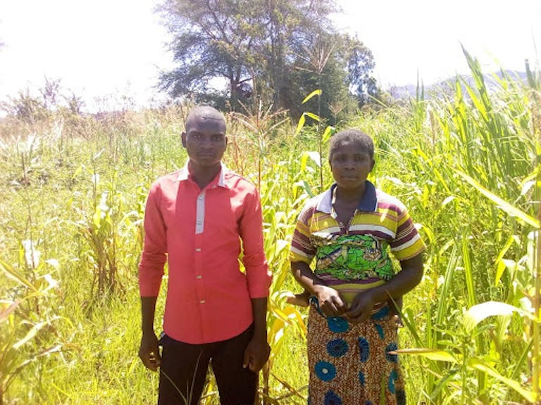 Ildephonse Kasinda, left, was embroiled in a disagreement with his neighbor for more than two years regarding an irrigation diversion that was causing his crops to die. He proposed a solution that he learned about in a play. Now he, his neighbor, and their wives word togethr to assure success for all. Pictured with Ildephonse is his neighbor's wife.