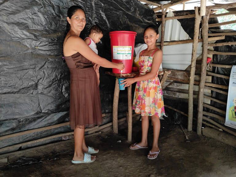 Mother with baby and older daughter drawing water from bucket with filter