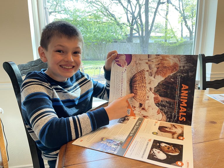 smiling boy in sweater at desk looking at FH gift catalog
