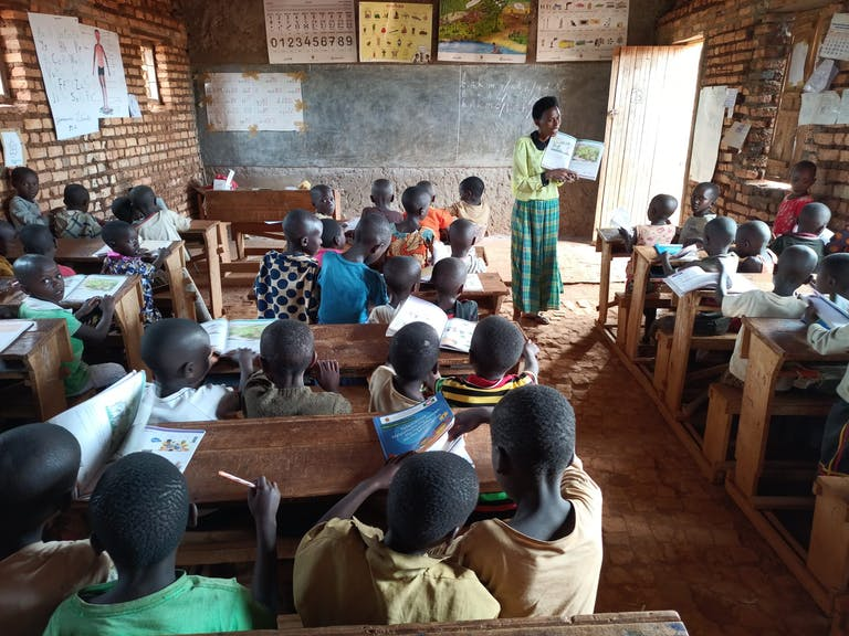 teacher in classroom in Burundi standing in front of the room reading a book with photos